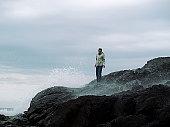 Woman on rocks in Tofino, British Columbia, wave aftermath