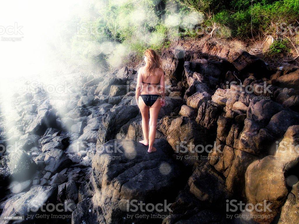woman on rocky shore stock photo