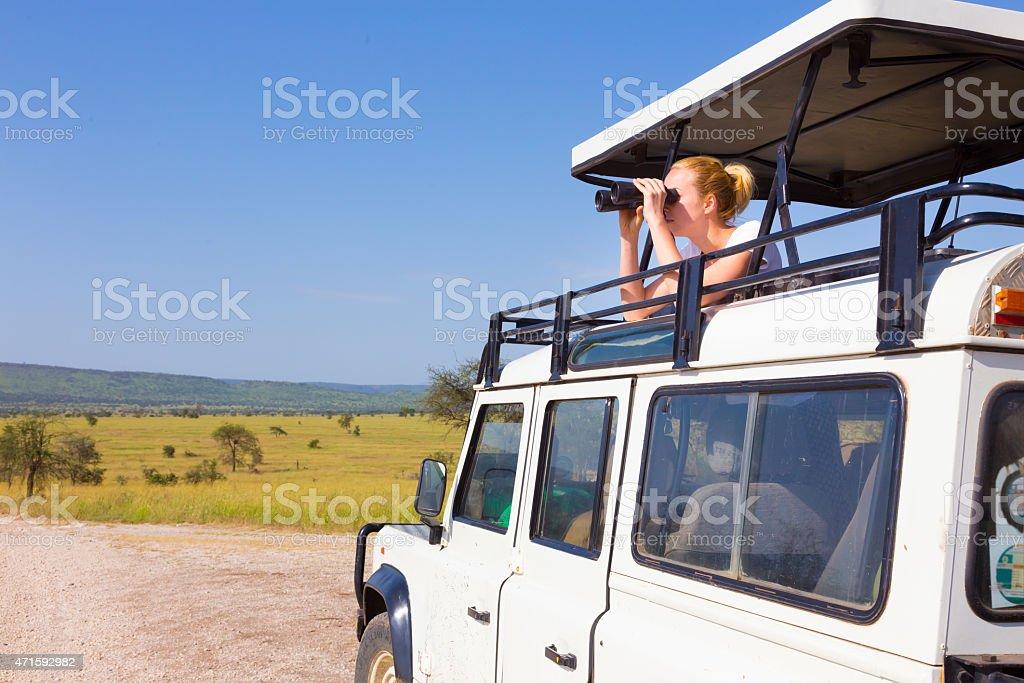 Woman on safari looking through binoculars. stock photo