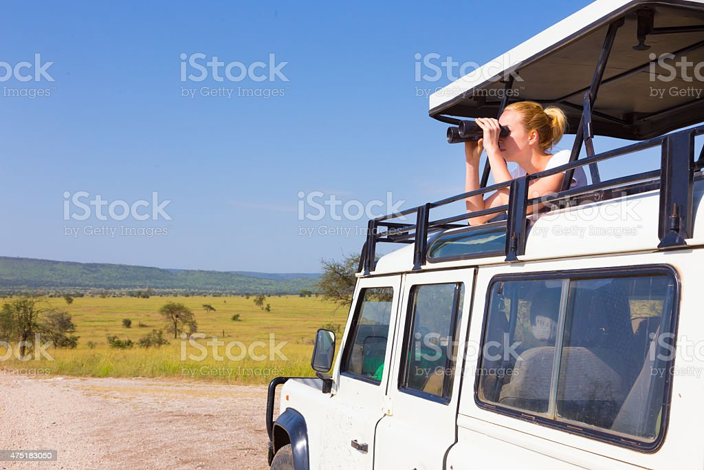 Woman on safari looking through binoculars. stock photo
