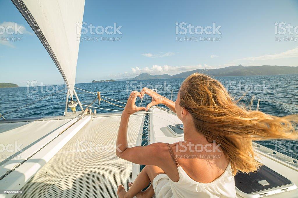 Woman on sailing boat makes heart shape finger frame stock photo