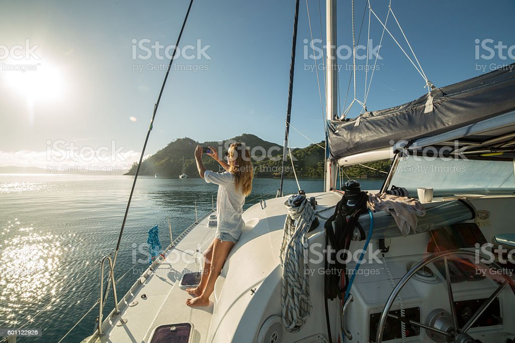 Woman on sailing boat photographing landscape with mobile phone stock photo