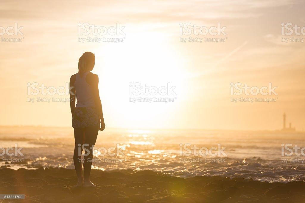 Woman on sandy beach watching sunset. stock photo