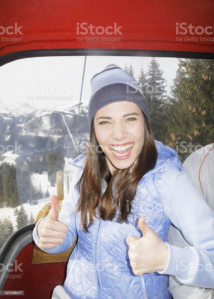 Woman on ski lift giving the thumbs up royalty-free stock photo