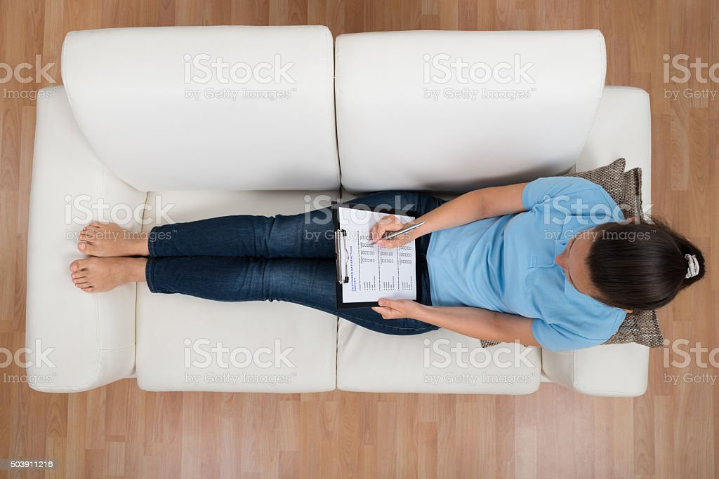 Woman On Sofa Filling Survey Form stock photo