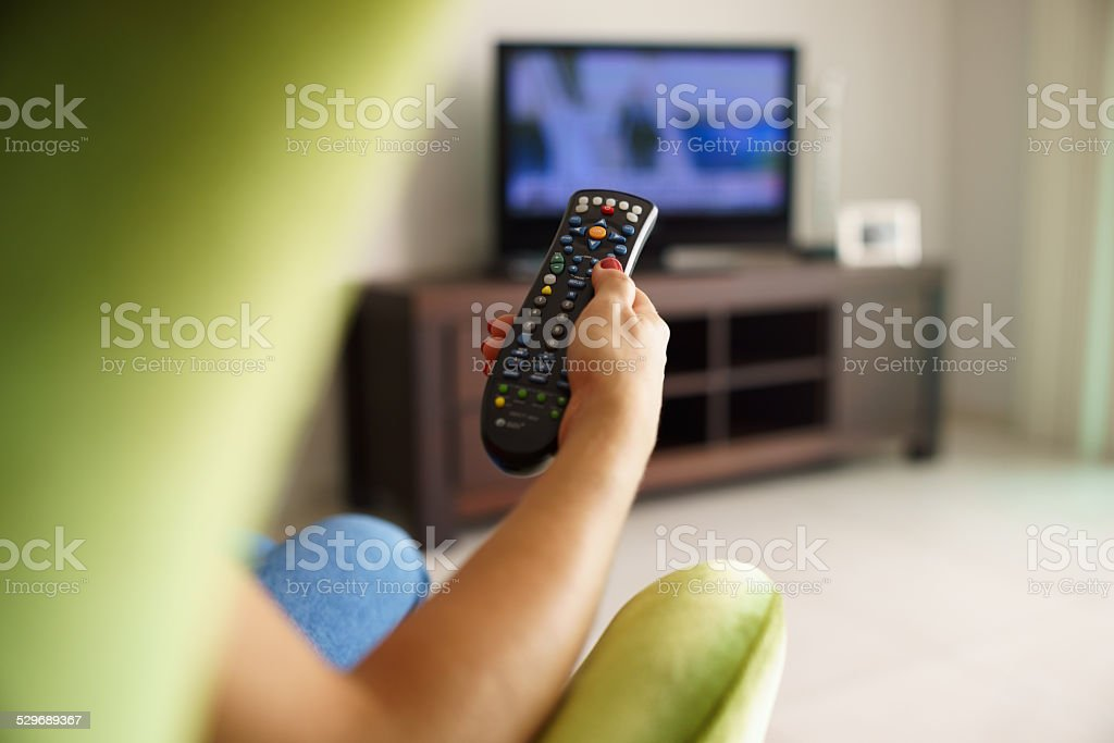 Woman on sofa watching tv changing channel with remote stock photo
