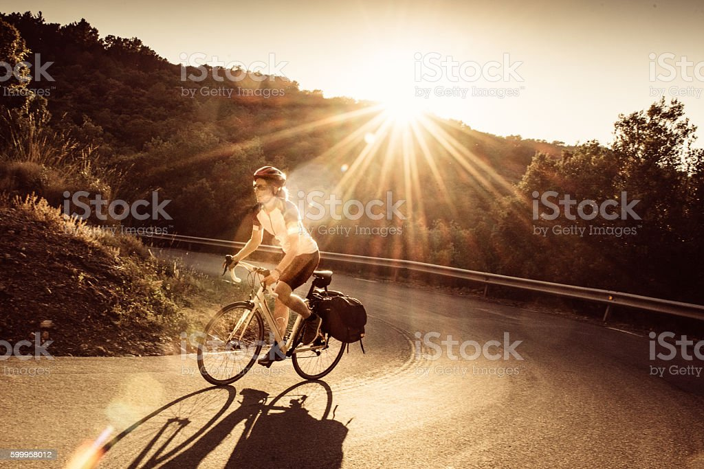 Woman on solo bicycle road trip stock photo