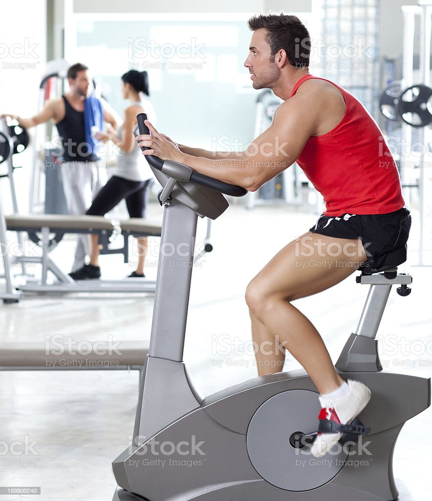 woman on stationary bicycle with personal trainer royalty-free stock photo