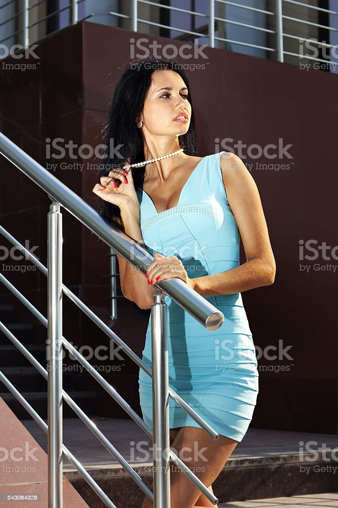 woman on steps in blue dress stock photo