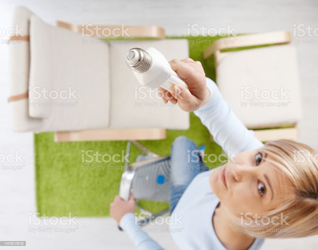 Woman on stool in room with green rug changing a light bulb stock photo