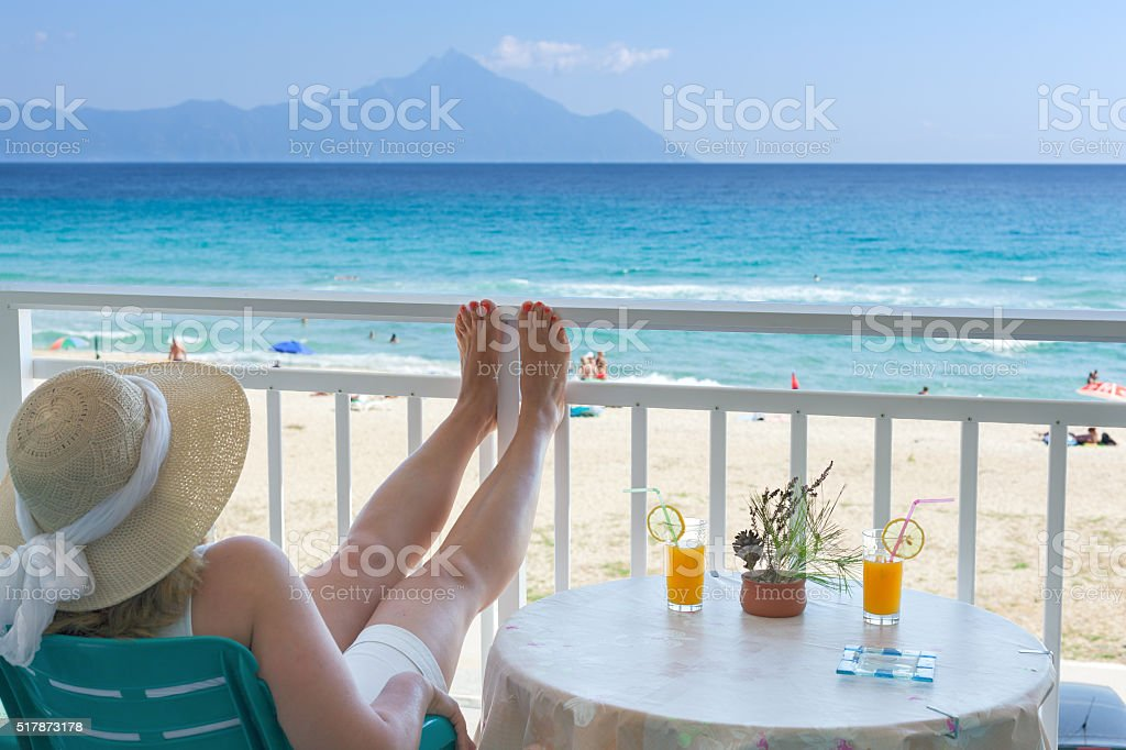 Woman on terrace looking to turquoise sea and sandy beach stock photo