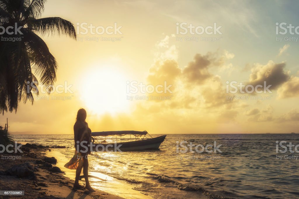 Woman on the beach against sunset stock photo