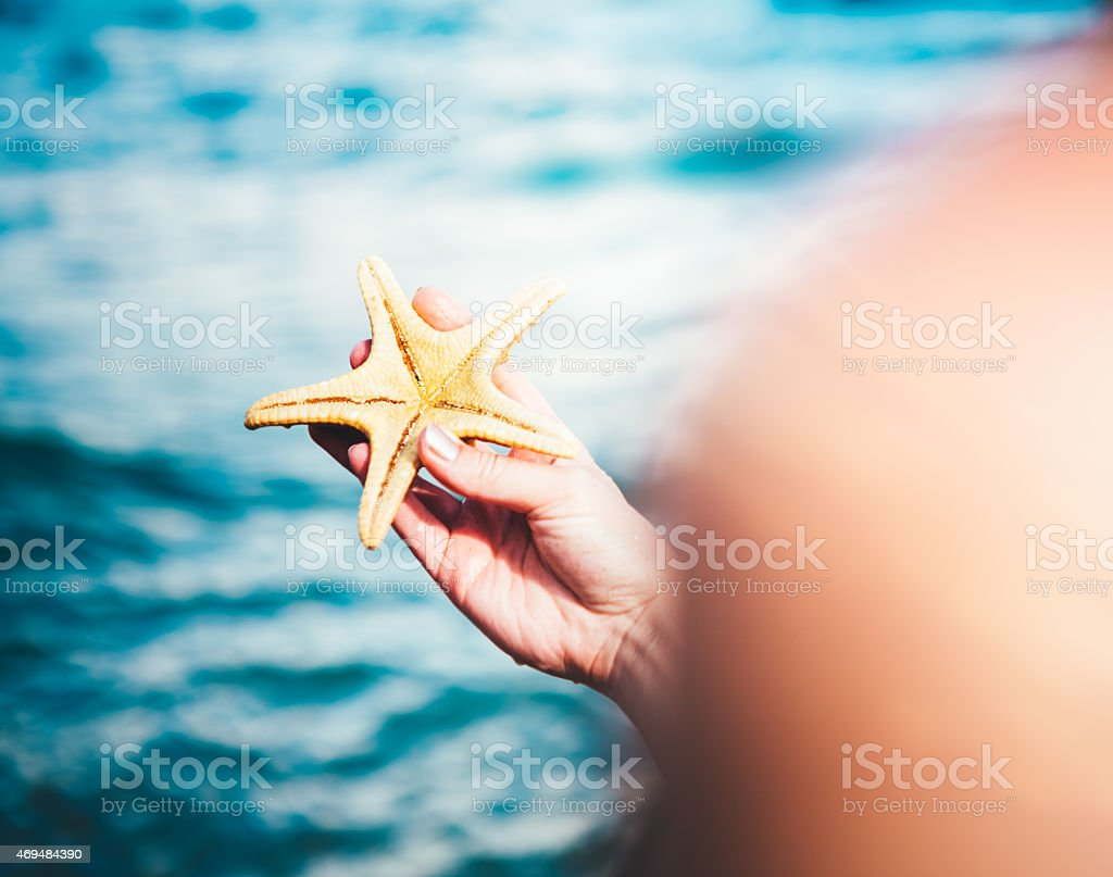Woman On The Beach Holding Starfish In Her Hand stock photo