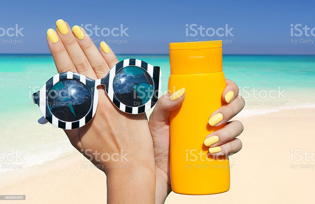 woman on the beach holding sunglasses and sunscreen lotion stock photo