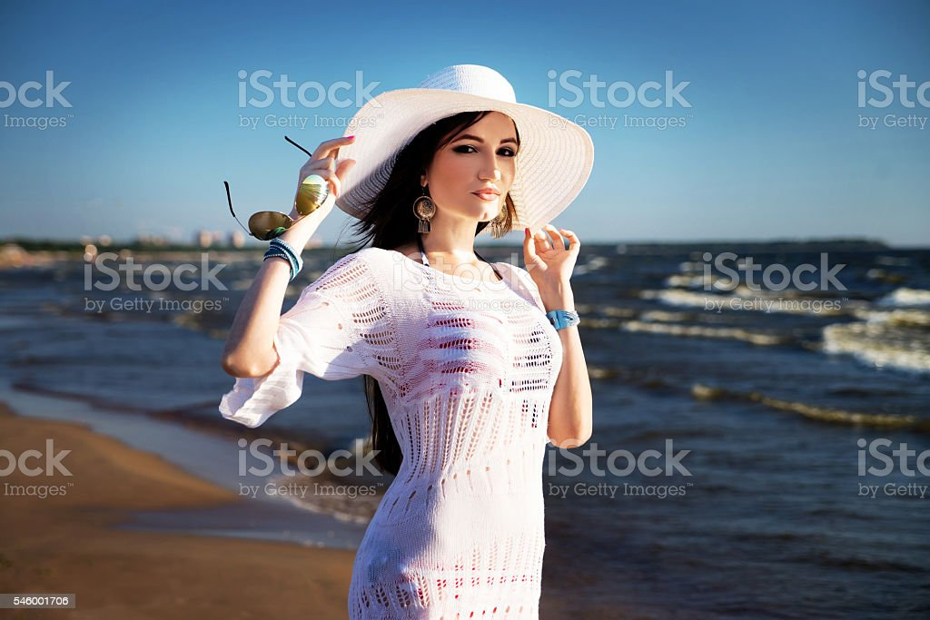 Woman on the beach in white hat and lace tunic stock photo