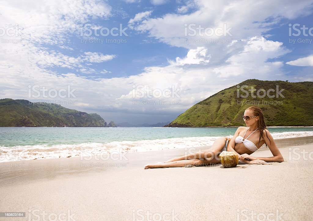 Woman on the beach with coconut royalty-free stock photo