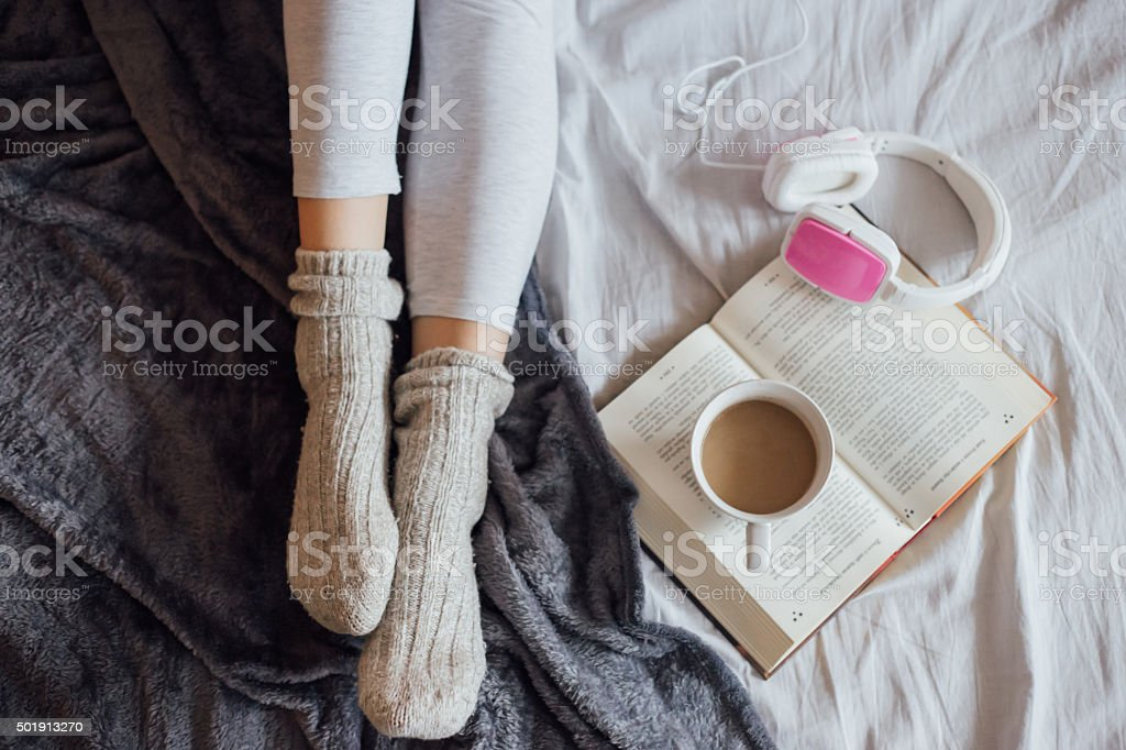 Woman on the bed with book, coffee and headphones stock photo
