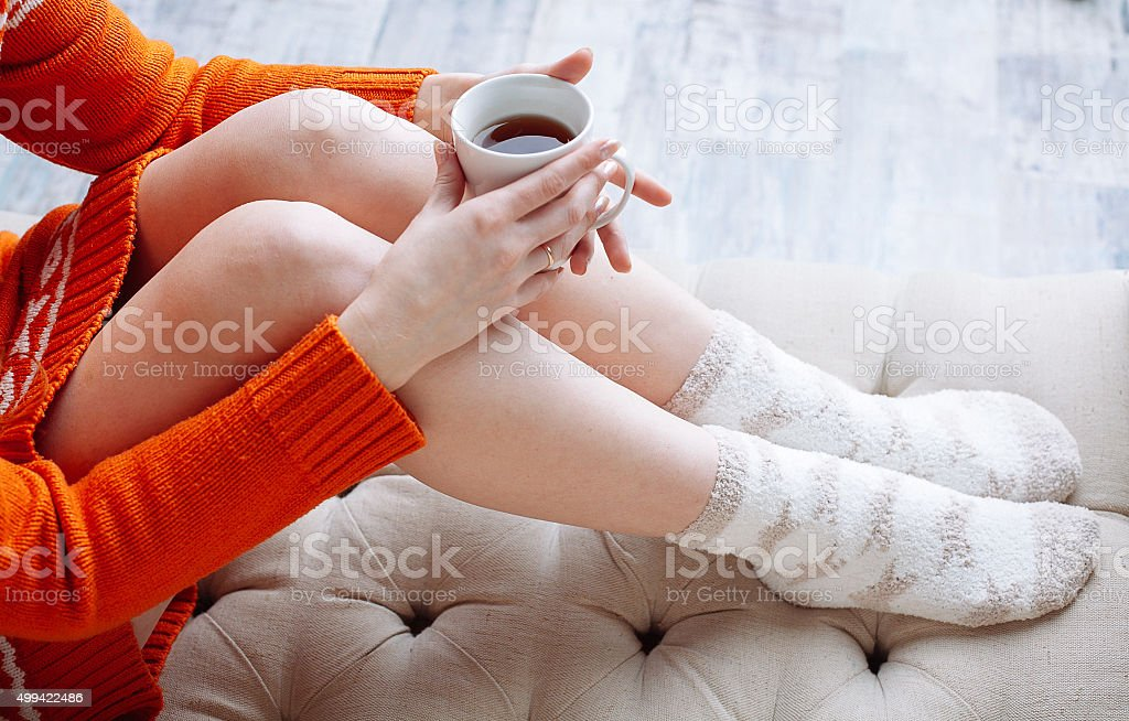 Woman on the bed with cup of tea stock photo