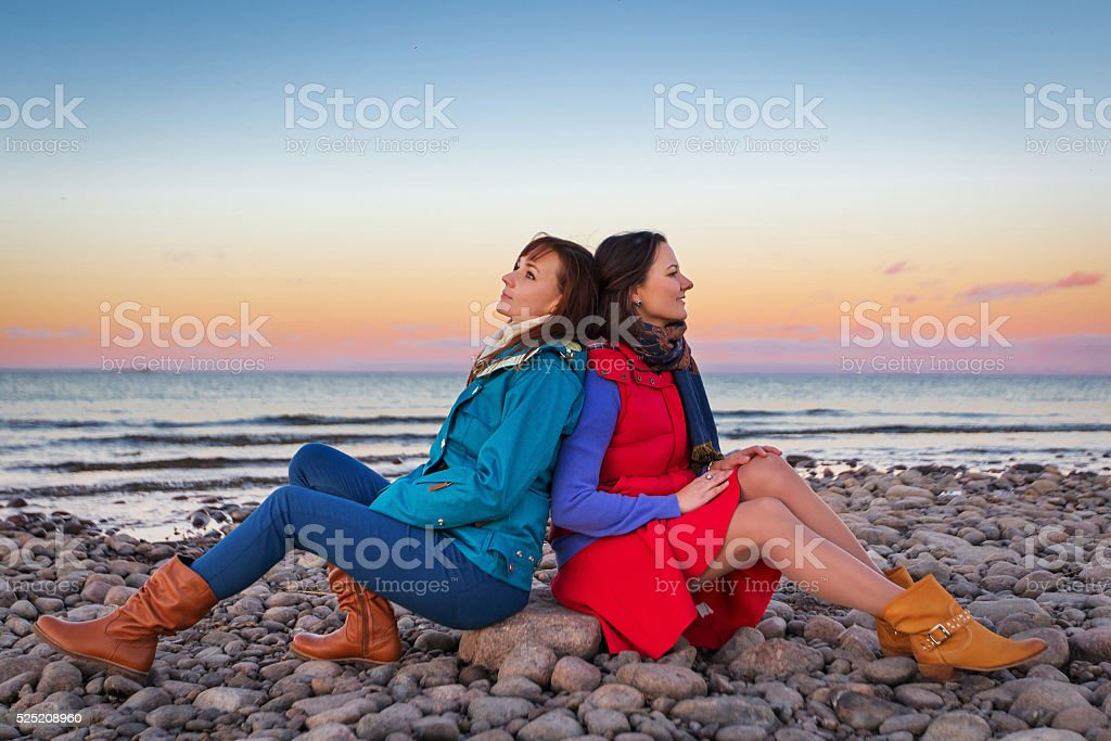 Woman on the cost of lake in sunset lights stock photo