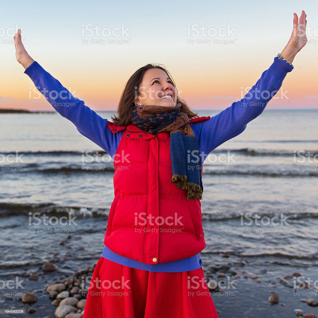 Woman on the cost of the lake in sunset lights stock photo