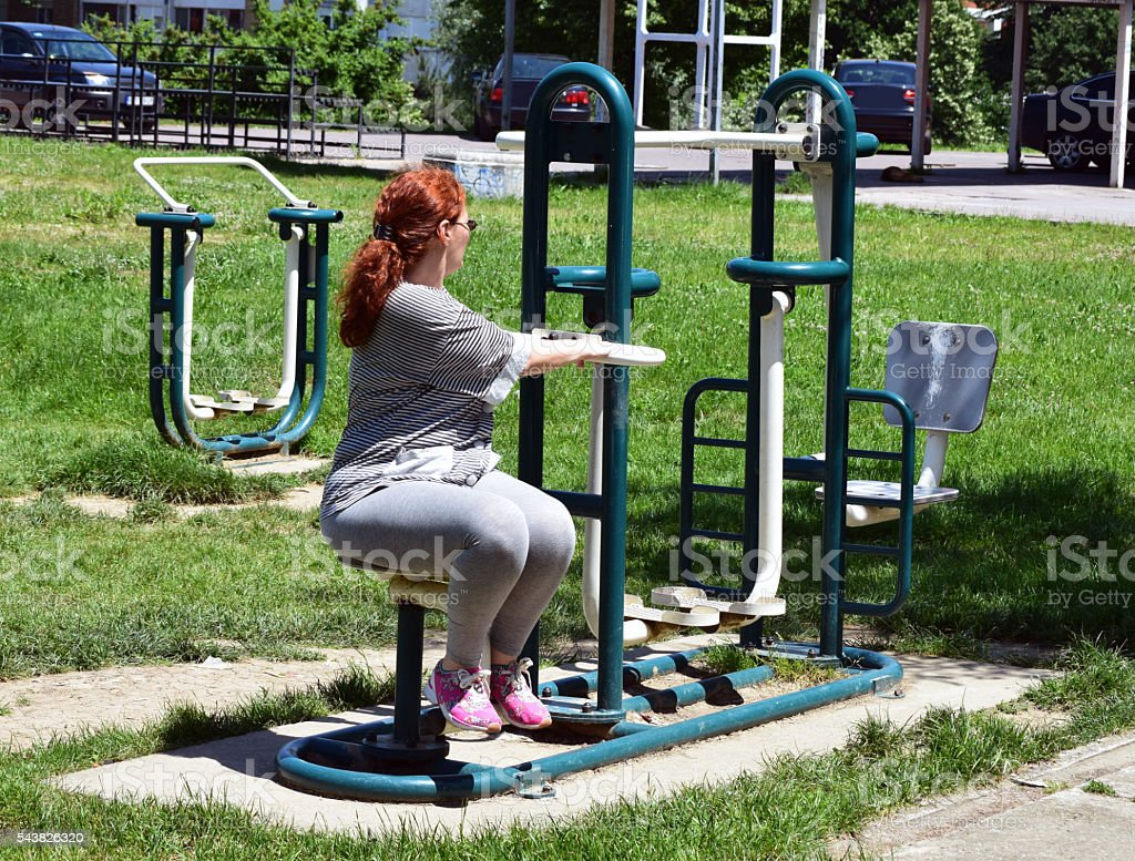 woman on the fitness equipment in the park stock photo