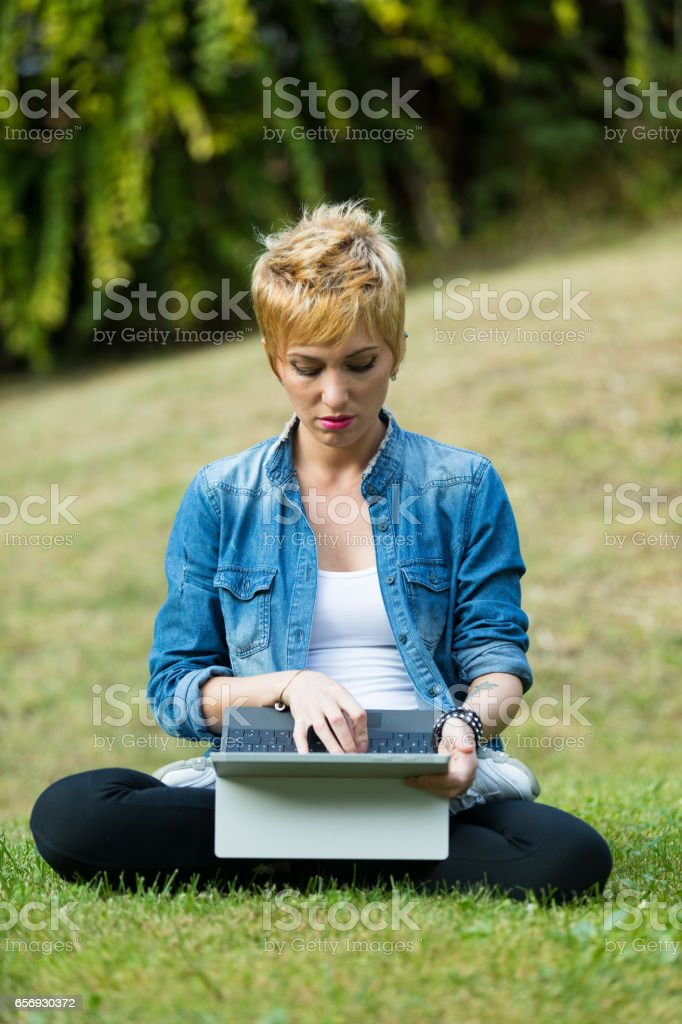 woman on the grass using a tablet sat in lotus position stock photo