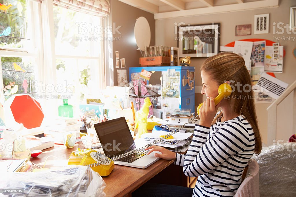 A woman on the phone at a cluttered desk at home stock photo