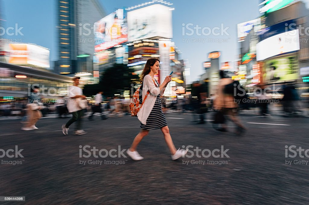 Woman on the phone at Shibuya crossing in Tokyo stock photo