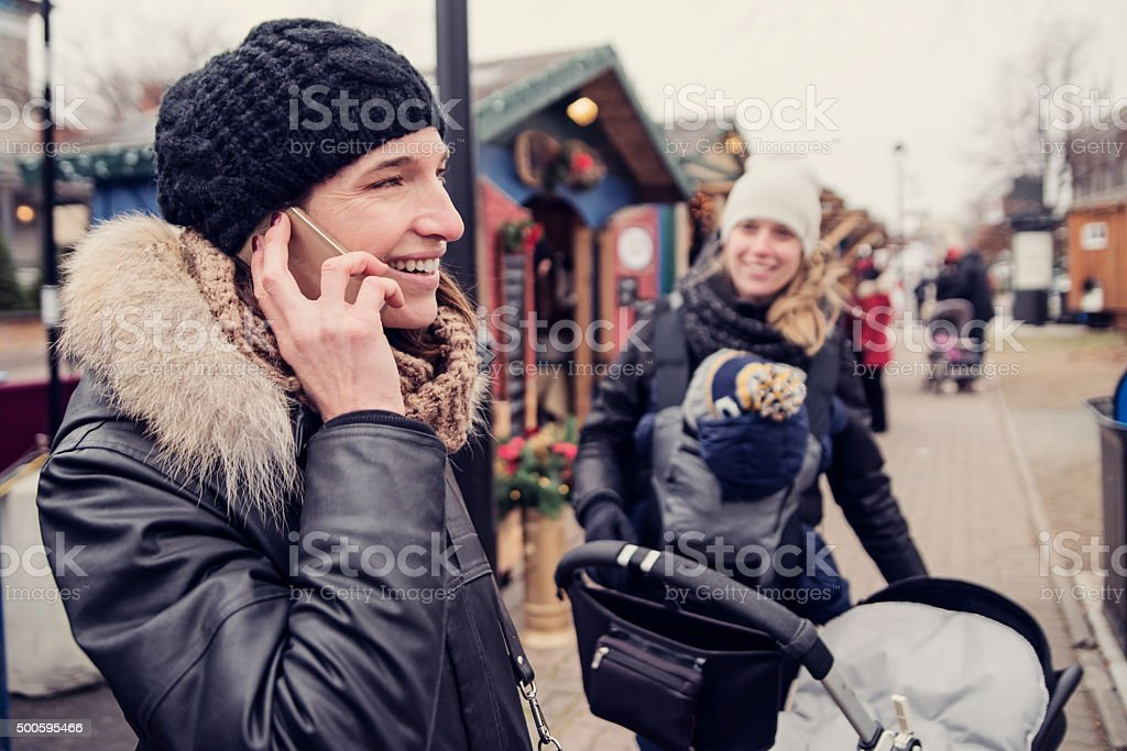 Woman on the phone in outdoors public market winter. stock photo