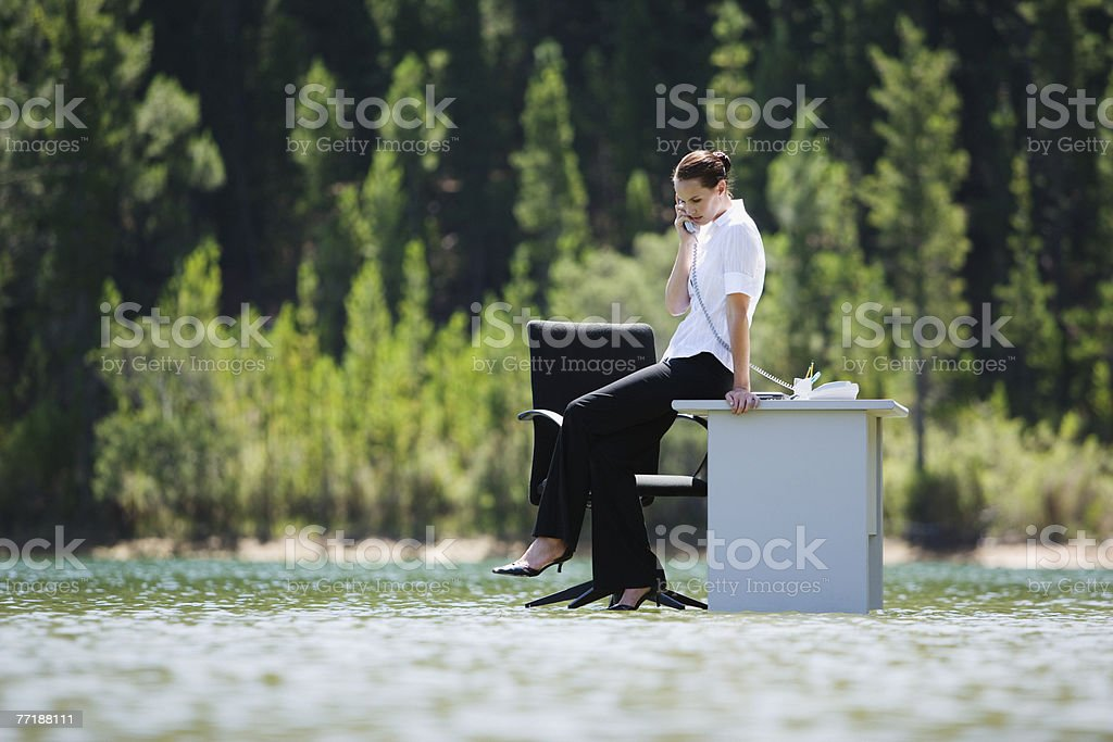 A woman on the phone on top of water royalty-free stock photo