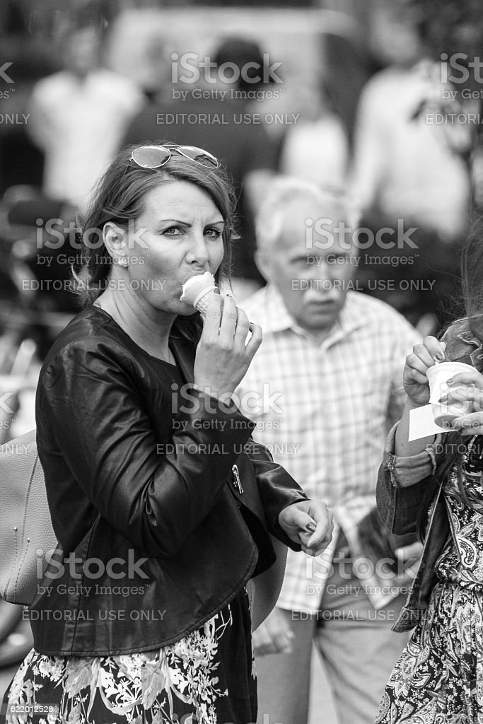 Woman on the street eating ice cream stock photo