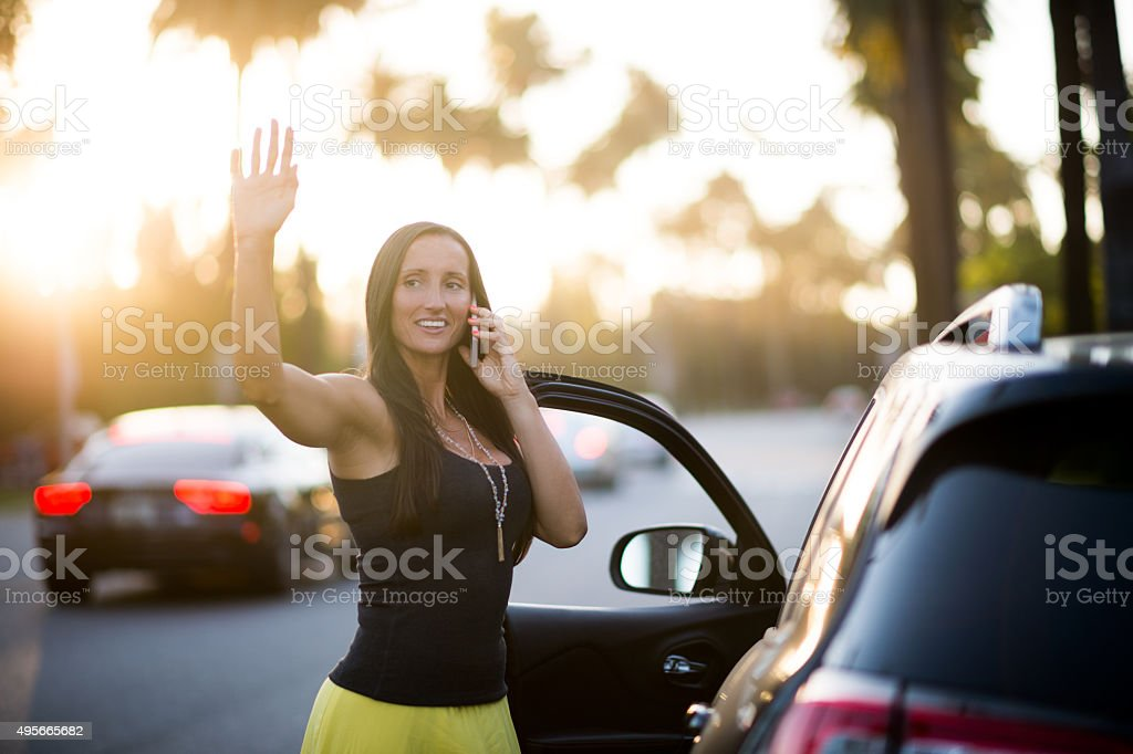 Woman on the street waving to someone stock photo