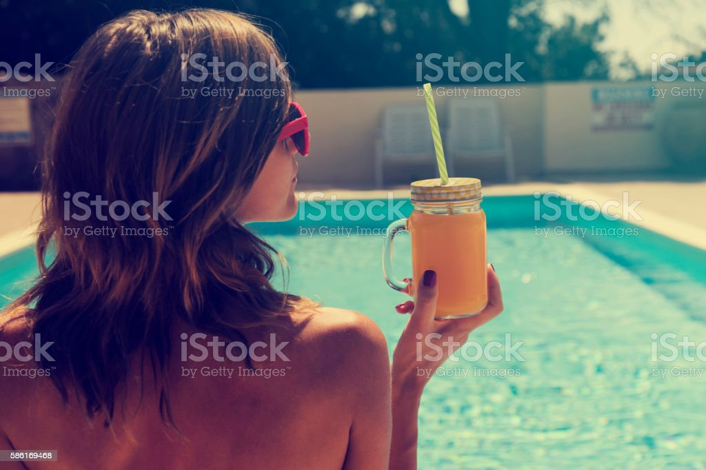 Woman on the swimming pool holding jar with orange juice. stock photo