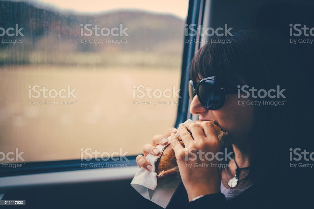 Woman on train eating a sandwich stock photo