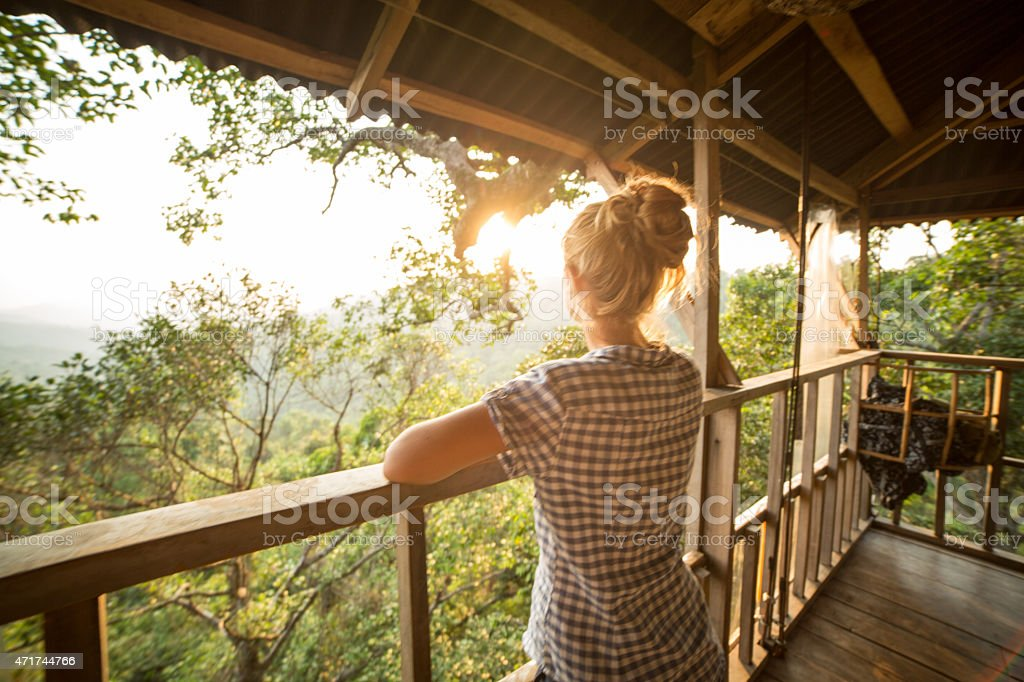 Woman on tree house looking at sunset stock photo