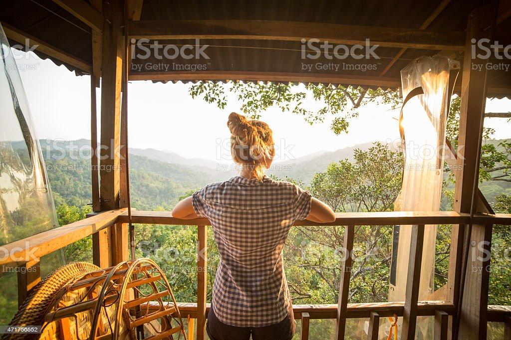 Woman on tree house watching sunset stock photo