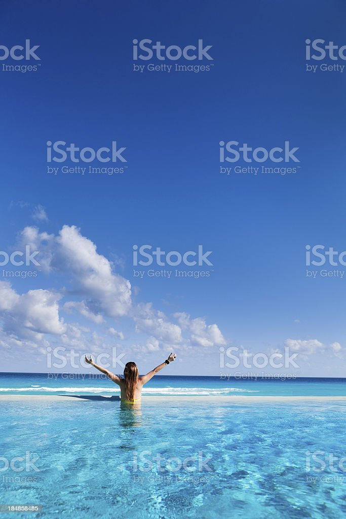 Woman on Vacation enjoying Infinity Pool in Caribbean Resort Hotel royalty-free stock photo