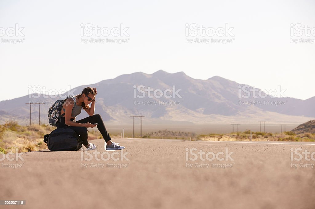 Woman On Vacation Hitchhiking Along Road Using Mobile Phone stock photo