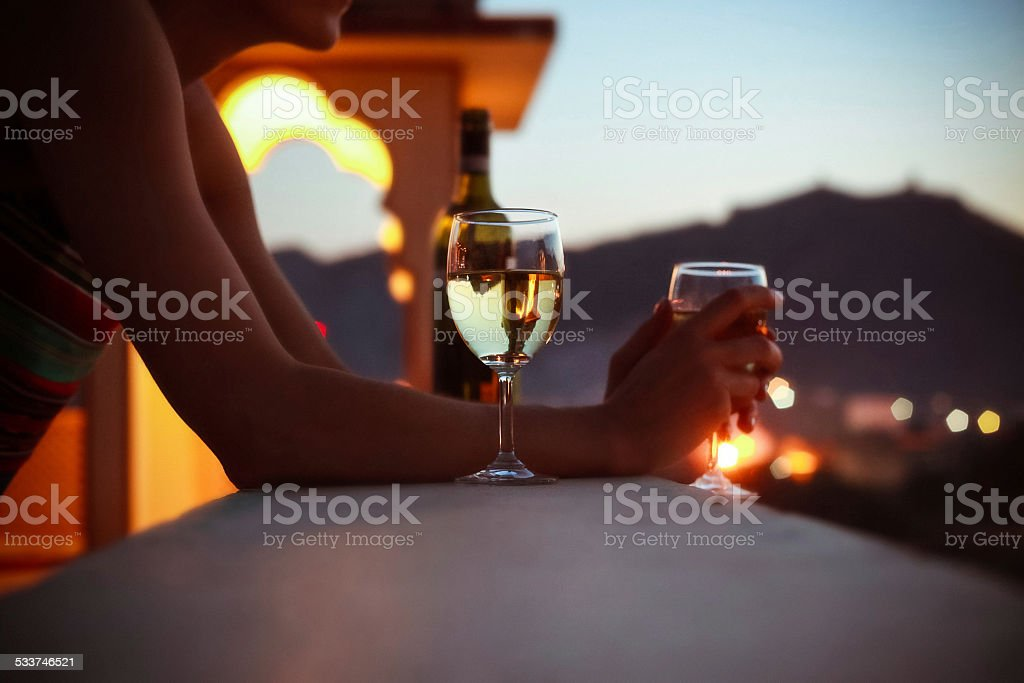 Woman on vacation in India drinking wine at sunset stock photo