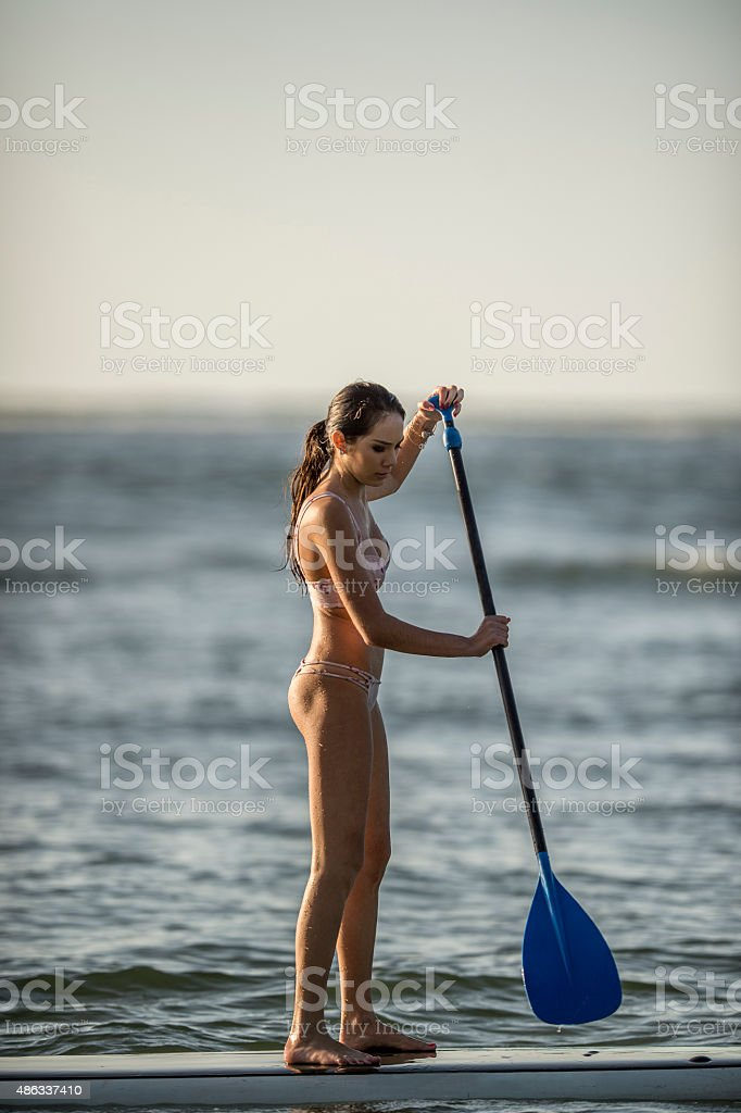 Woman on Vacation is Stand Up Paddle Boarding stock photo