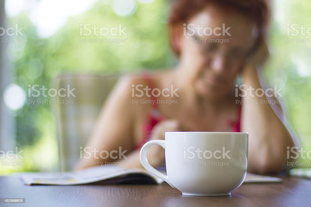 Woman on vacation reading newspaper, drinking coffee royalty-free stock photo