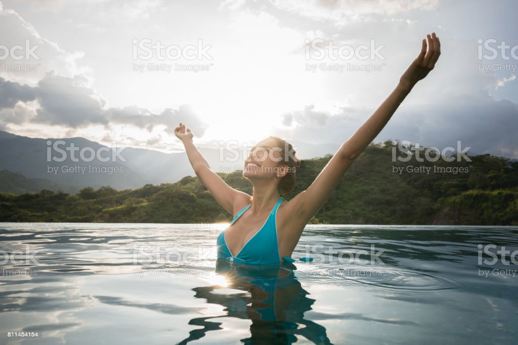 Woman on vacations looking very happy in the swimming pool stock photo