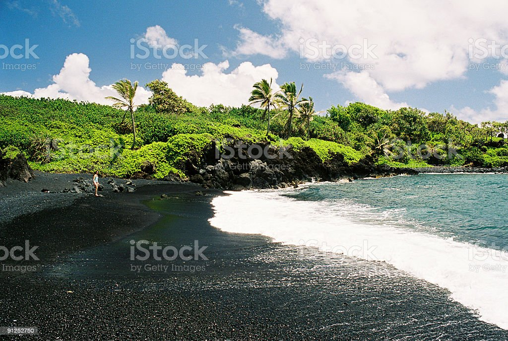 Woman on Wainapanapa Maui Hawaii black sand beach stock photo