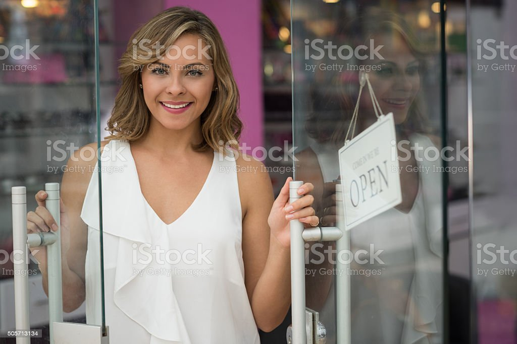 Woman opening a beauty store stock photo
