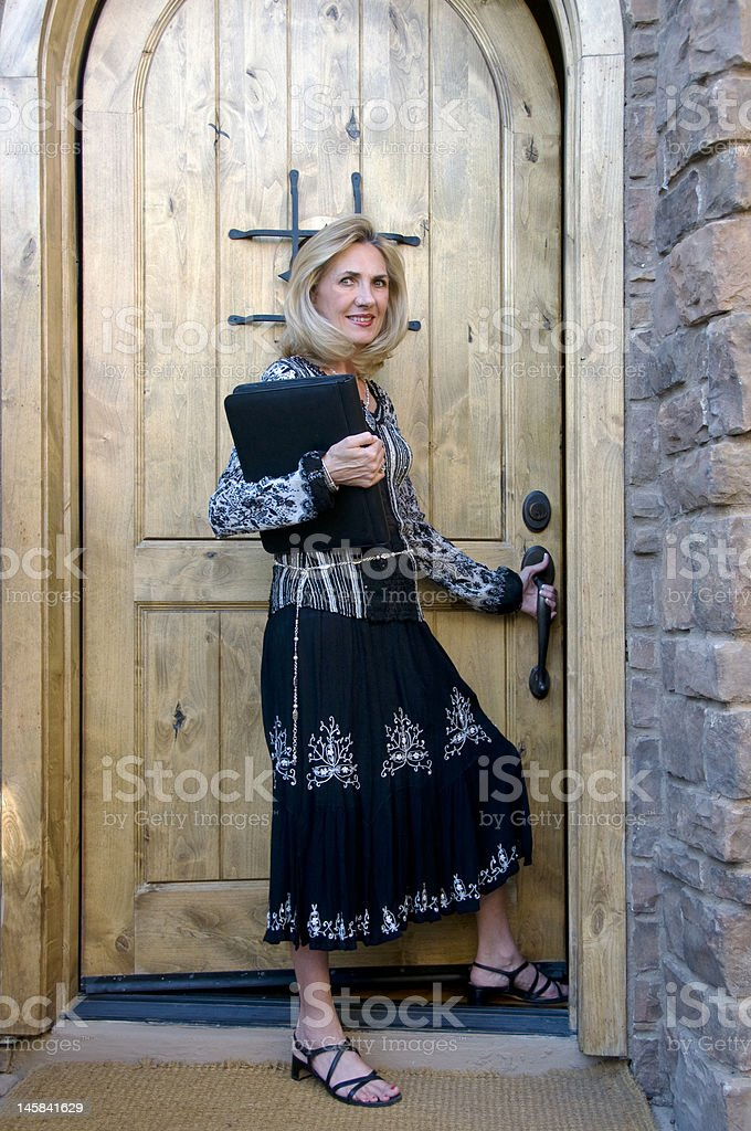 Woman opening a door royalty-free stock photo