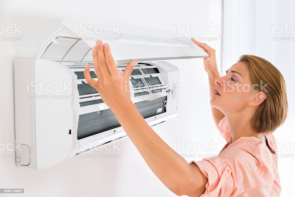 Woman Opening Air Conditioner stock photo