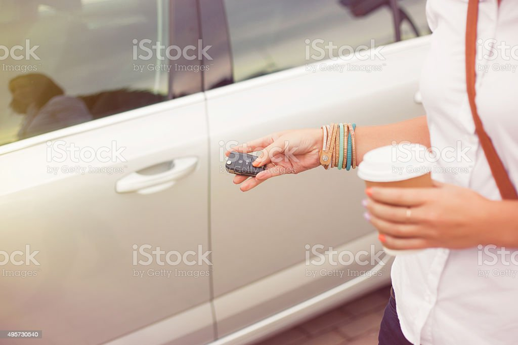 Woman opening car with keys while holding coffee stock photo