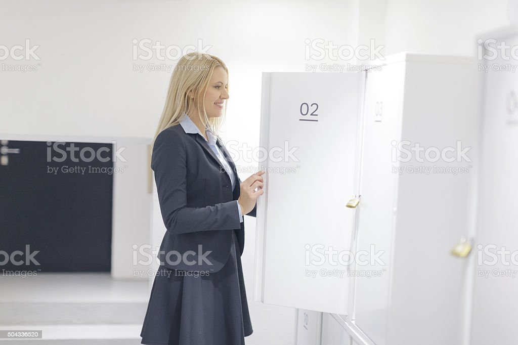 Woman opening locker stock photo