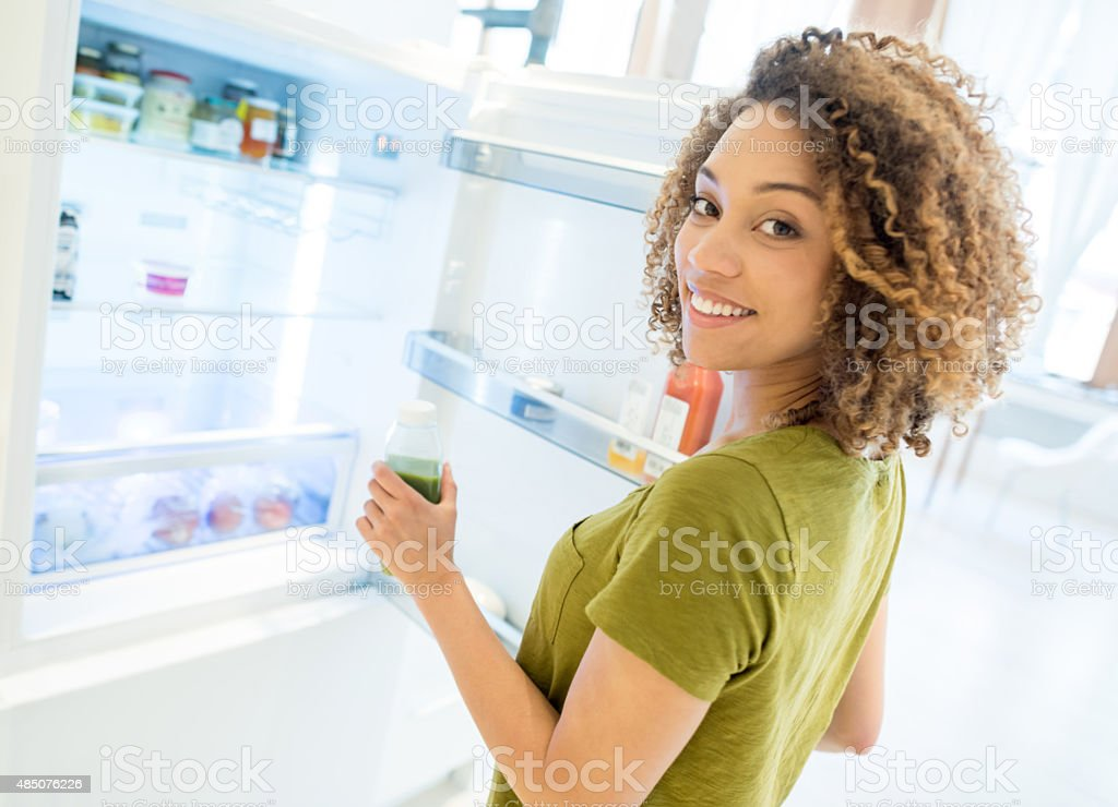 Woman opening the fridge stock photo