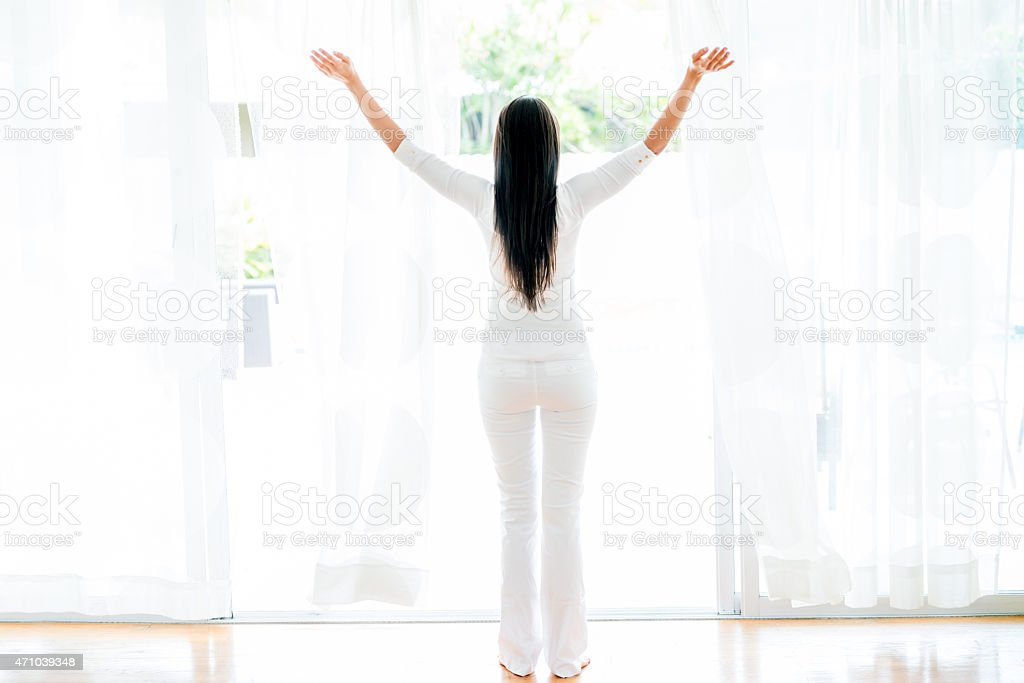 Woman opening the windows at home stock photo